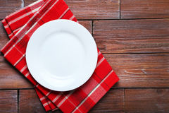 Empty plate. With napkin on brown wooden table Stock Images