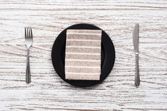 Empty plate napkin fork knife silverware white wooden table back Royalty Free Stock Photography