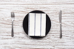 Empty plate napkin fork knife silverware white wooden table back Royalty Free Stock Images