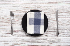 Empty plate napkin fork knife silverware white wooden table back Royalty Free Stock Photo
