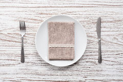 Empty plate napkin fork knife silverware white wooden table background Stock Image