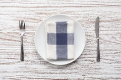 Empty plate napkin fork knife silverware white wooden table background Stock Photos