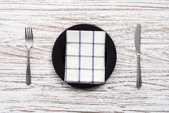Empty plate napkin fork knife silverware white wooden table background Stock Photo