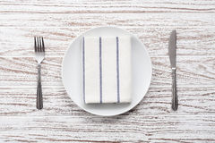 Empty plate napkin fork knife silverware white wooden table background Royalty Free Stock Photos