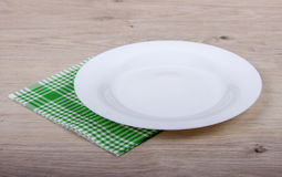 Empty plate and napkin. On a wooden table background royalty free stock photo