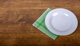 Empty plate and napkin. On a wooden table background Stock Photography