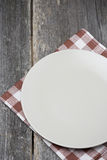 Empty plate on a napkin on wooden table, concept Stock Images