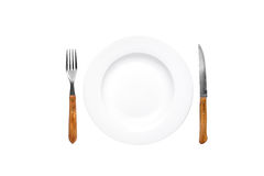 Empty plate old rustic fork and knife isolated over white background Royalty Free Stock Image
