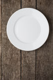 Empty plate on old wooden background. Top view Stock Image