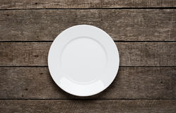 Empty plate on old wooden background. Top view Royalty Free Stock Photos