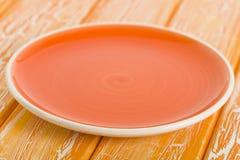Empty Plate. Orange round  on a crackled orange wooden background Stock Photo