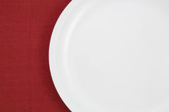 A empty plate on red tablecloth Stock Photos