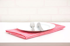 Empty plate on red tablecloth. Over table with brick wallpaper background Royalty Free Stock Images