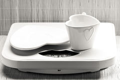 Empty plate saucer and mug cup on weighing scale. Royalty Free Stock Image
