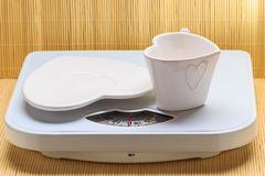 Empty plate saucer and mug cup on weighing scale. Stock Images