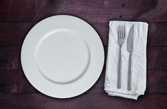 Empty plate and silverware on mahogany wood