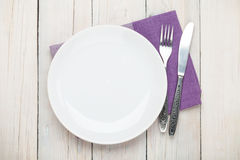 Empty plate and silverware. Over white wooden table background. View from above Stock Photography