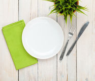 Empty plate and silverware over white wooden table background Royalty Free Stock Photos