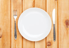 Empty plate and silverware over wooden table background Royalty Free Stock Image