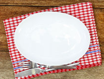 Empty plate, silverware and towel over wooden table Stock Images