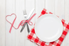 Empty plate, silverware and valentines day heart shaped ribbon Stock Photos