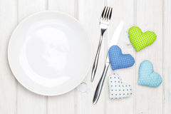 Empty plate, silverware and valentines day toy hearts Royalty Free Stock Image