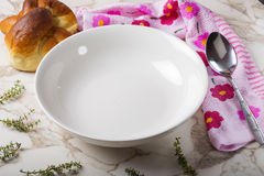 Empty plate for soup with spoon, bread and herbs Stock Image