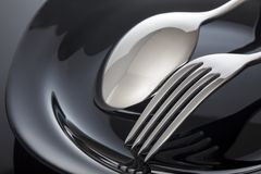 Empty plate with spoon and fork on a black background.  Royalty Free Stock Photography