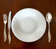 Empty plate with spoon, fork and knife on wooden background Stock Photos