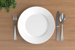 Empty plate, spoon, fork and knife Royalty Free Stock Images