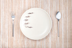 Empty plate with spoon and fork Stock Image