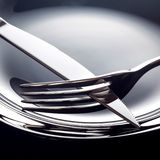 Empty plate with spoon, knife and fork on a black background.  royalty free stock photos