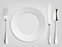 Empty plate with spoon, knife and fork Stock Photos