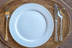 Empty plate with spoon, knife and fork on wooden natural backgro Royalty Free Stock Photo