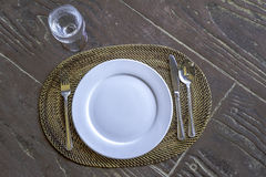 Empty plate with spoon, knife and fork on wooden natural backgro Royalty Free Stock Photos