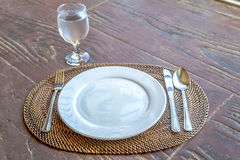 Empty plate with spoon, knife and fork on wooden natural backgro Stock Images
