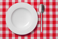Empty plate. And a spoon on red and white tablecloth Stock Photos
