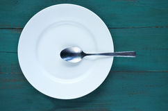 Empty plate with spoon on wooden background Royalty Free Stock Photo