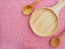 Empty plate and spoons on red checked tablecloth Stock Photography