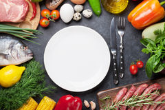 Empty plate surrounded by cooking ingredients Royalty Free Stock Images