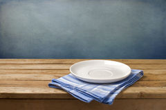 Empty plate on tablecloth. On wooden table over grunge blue background Royalty Free Stock Photo