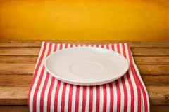 Empty plate on tablecloth. Over grunge yellow background Stock Images
