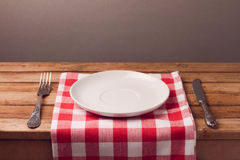 Empty plate with tablecloth and silverware on wooden table. Empty plate with checked tablecloth and silverware on wooden table Royalty Free Stock Photography