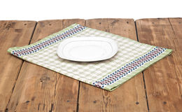 Empty plate on tablecloth. On wooden table Stock Images