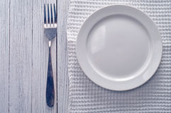 Empty plate. On tablecloth on wooden table Stock Photos