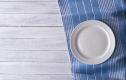 Empty plate. On tablecloth on wooden table Royalty Free Stock Photos