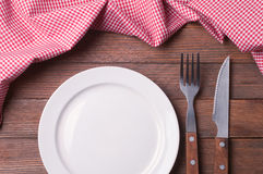 Empty plate. On tablecloth on wooden table Royalty Free Stock Photography