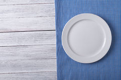 Empty plate. On tablecloth on wooden table Stock Image