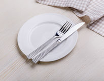 Empty plate on tablecloth. On wooden table Royalty Free Stock Photo