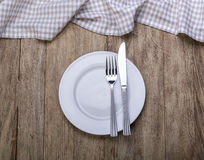 Empty plate on tablecloth. On wooden table Royalty Free Stock Image